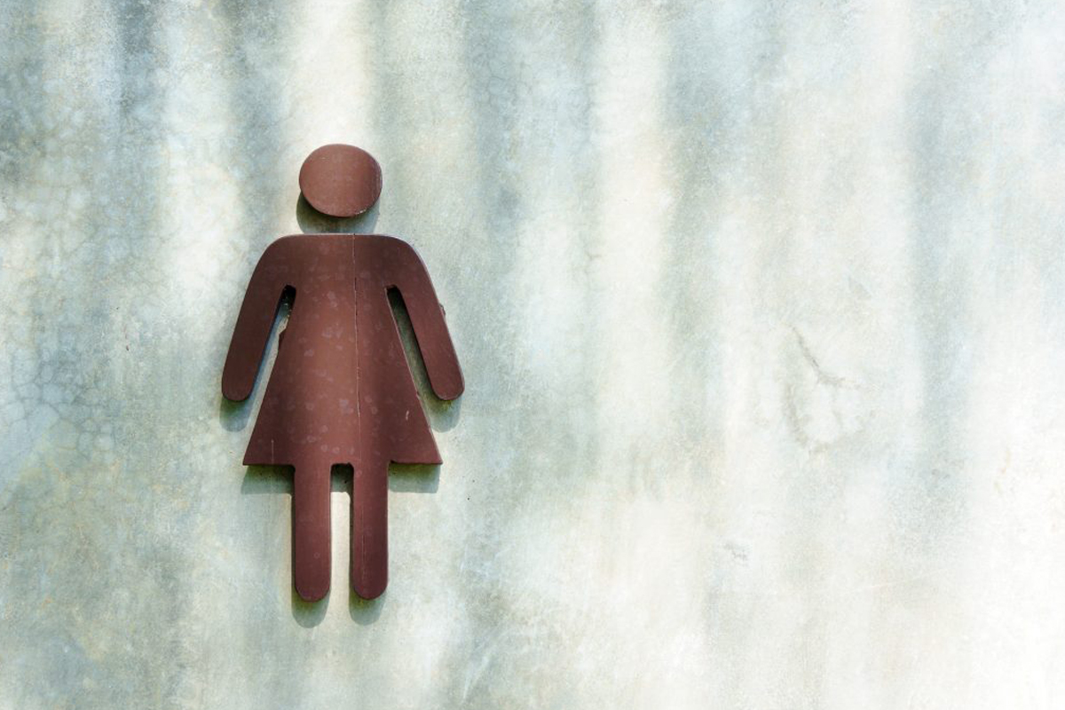 female symbol or sign on the cement wall in front of the lavatory or toilet